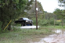 A high-profile vehicle makes its way through floodwaters in Sam Houston Lake Estates in order to travel to a bus stop where a Tarkington ISD school bus picks up and drops off children for school.