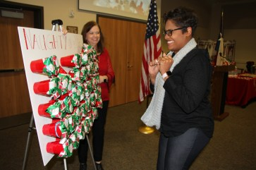 Kristy Fontenette tries to pick the right cup in the Dayton Chamber's Naughty or Nice game at the Dec. 4 luncheon.