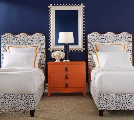 White and blue twin beds with orange table