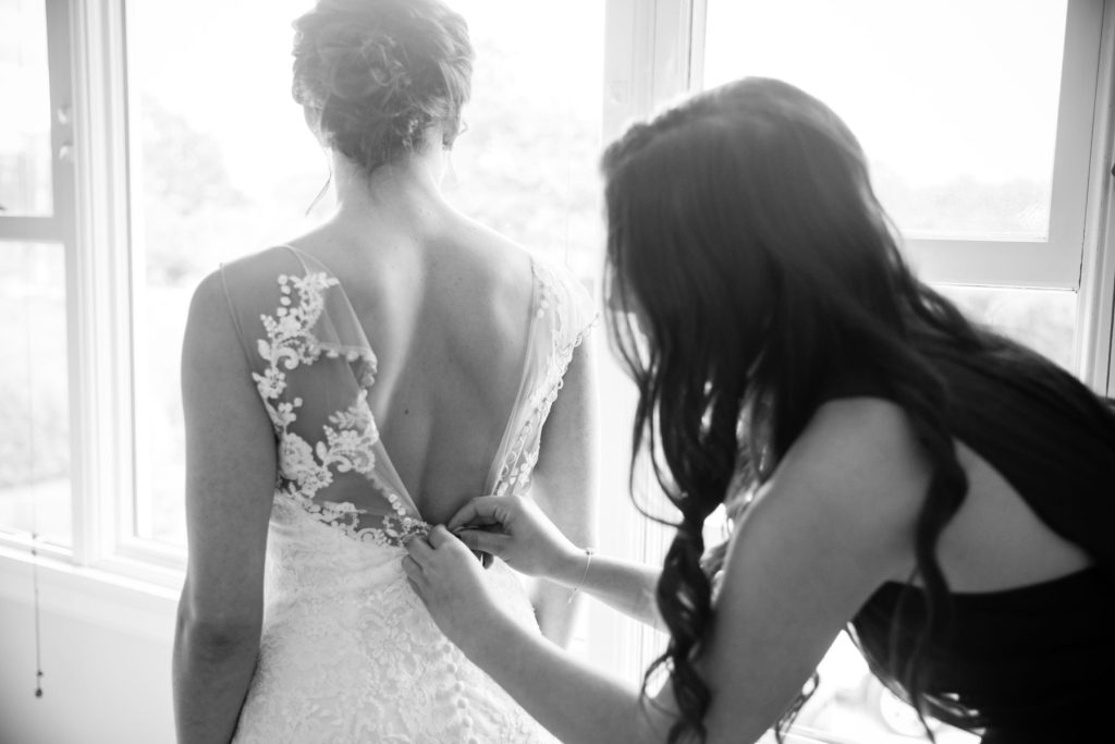 Tia and Michael | buttoning up the wedding dress