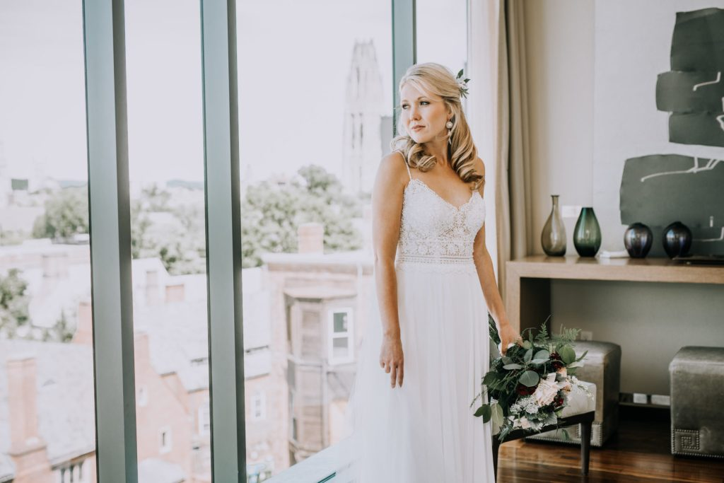Sasha and Michael | Bride with flowers looking out the window