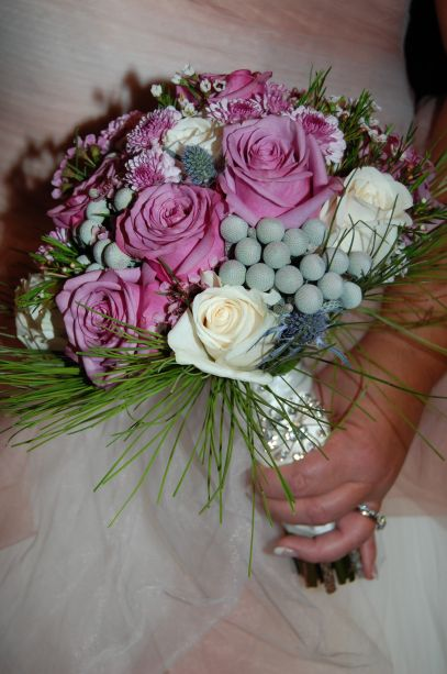 Brides bouquet in cool water and ivory roses, brunia, thistle, with a pine halo.