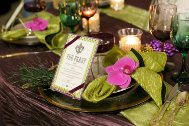 Table set with Phalaenopsis orchid, beautiful linens, custom stationary, purple stemware and candles
