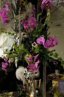 Orchids, callas bells of ireland, manzanita, and spanish moss in a tall trumpet vase with beads and masks