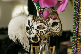 Phalaenopsis orchids, masks and beads hanging from the centerpieces to provide the perfect Mardi Gras look