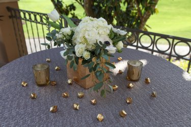 Cocktail tables with gold leaf centerpiece of white hydrangea, eucalyptus, anemones, tulips and calla lily, gold mercury and gems