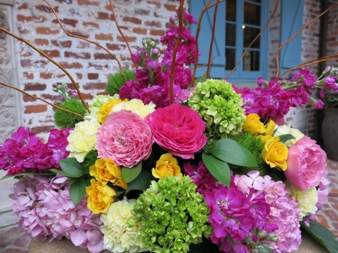 An ombre of pink Garden Roses, Stock, and Hydrangea were accompanied by pops of bright yellow Spray Roses, and green trick