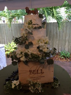 Elegant cake with floral and greens on top of a wine crate