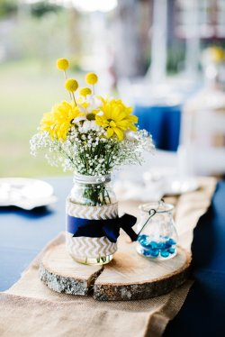 Table setting with wood slice, chevron burlap and navy ribbons with a handful of wildflowers and billy balls