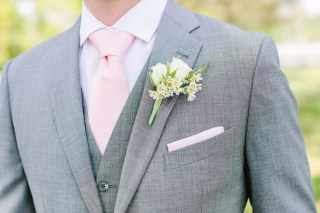 Groom's boutonniere of ivory spray roses and wax flower