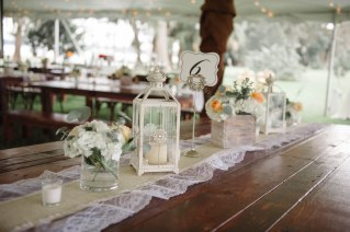 We paired our white lanterns with our white wash boxes, filled with white Hydrangea, Euchs, and Juliets for elegant reception table decor.