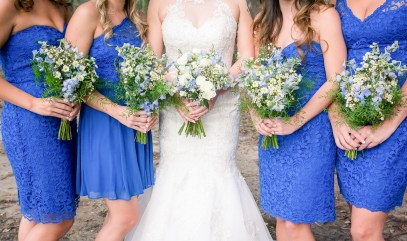 Our bride with her white Wildflower Bridal Bouquet with pops of Blue Delphinium and Corn Flower, paired with our Maids' bouquets filled with white Asters, Greens, and blue Delphinium.
