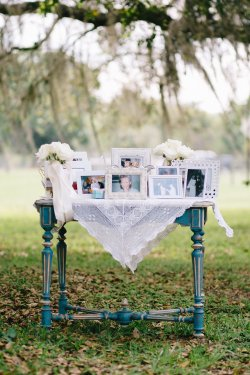 Memory table during ceremony with white roses with streaming ribbons.