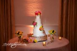Cake floral of coral charm peonies, craspedia, golden galaxy spray roses, orange babe spray roses, orange sunset garden roses, jade green hypericum, and green amaranthus.