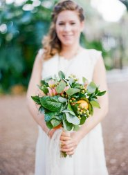 Bridal bouquet filled with cuties, hypericum berries, peach alstroemeria, and greens.