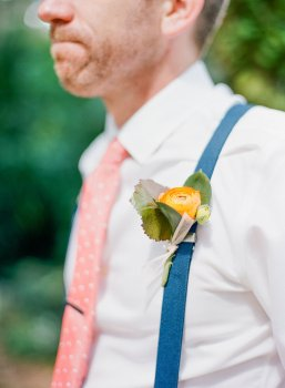 Groom's boutonniere with an orange ranunculus and greens.