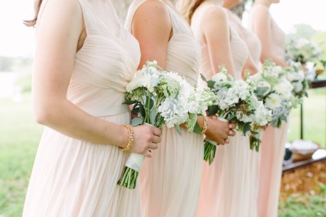 Elegant blush dresses with green and white bouquets for the maids.