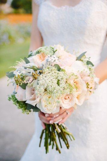 Bridal bouquet of Juliet garden roses, ranunculus, Queens Ann lace, dusty miller, spray roses and eucalyptus.