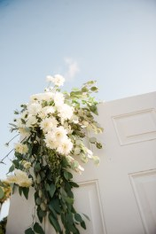 Ceremony doors with green and white floral accents