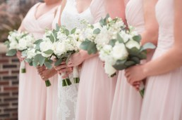 Brides bouquet was created using white football mums, white ranunculus, white stock, white tibet roses, silver dollar eucalyptus, and white majolika spray roses. The bridesmaids bouquets were created with the same floral but on a smaller scale.