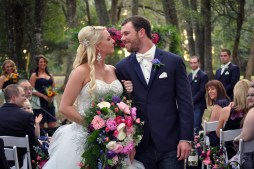 The bride and groom after 'I-do's', showing of the wildflower bouquet of ivy, mini sunflowers, pink snapdragons, bright pink peonies, bright blue delphinium, queens ann, dark purple lisianthus,bubble gum pink spray, italian ruscus, thistle, and pink garden roses, and grooms bout with ivy, pink freesia, and blue delphinium blooms.
