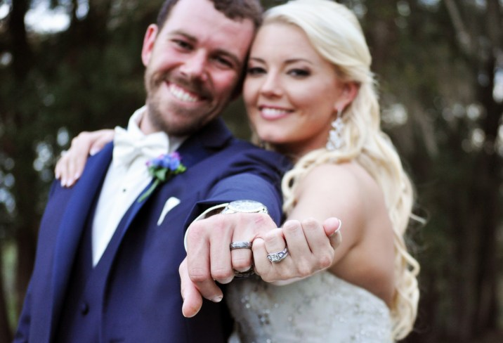 Our bride and groom showing off their rings and rustic style.