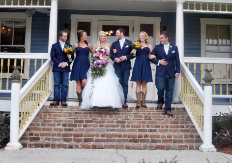 The bridal party showing off their rustic style with cowboy boots, navy color scheme and wildflower bouquets.