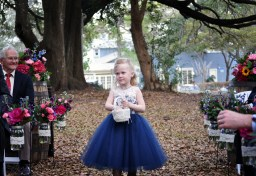 The lovely flower girl walking down the aisle lined with mason jars filled with hot pink peonies, bubble gum spray roses, bright blue delphinium, purple stock, greens and pink garden roses.