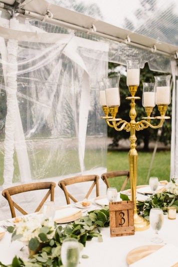 Gold candelabras with garland and gold mercury votives.