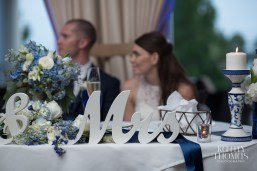 The bride and groom enjoy their sweetheart table with matching candle holders and repurposed bouquet