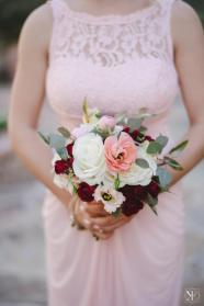 Maids carrying bouquets of blush ranunculus, white anemone, roses and eucalyptus.