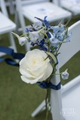 White rose and blue delphinium chair ties line the aisle