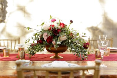 Gold compote with garden style arrangement of peach, pink, ivory and flowing greens.