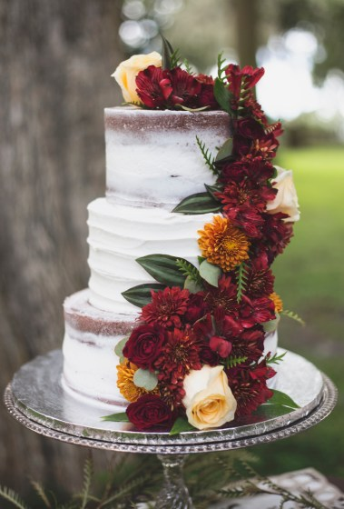 Cake floral with yellow mum and burgundy mums, ivory standard roses, and greens.