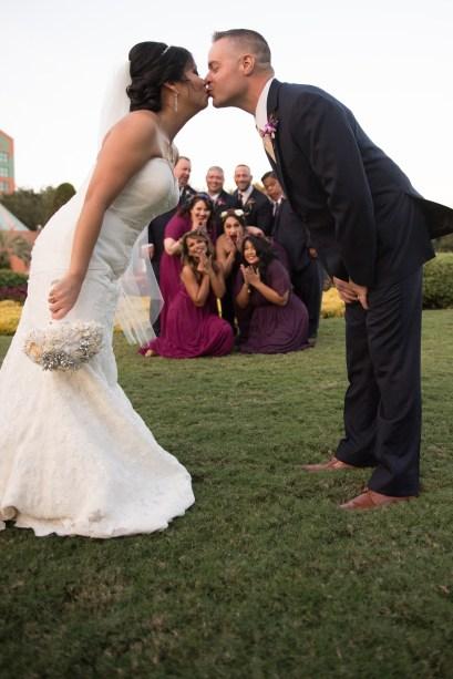 Bridal party peeking through bride and groom kissing