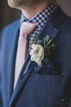 Grooms boutonniere with white ranunculus, thistle, and seed eucalyptus.