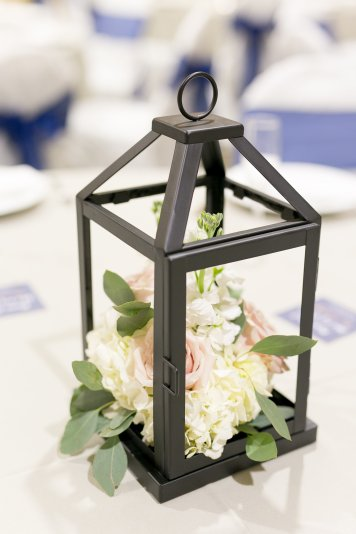 Black lanterns with floral of blush, greenery and ivory for a classic garden feel.