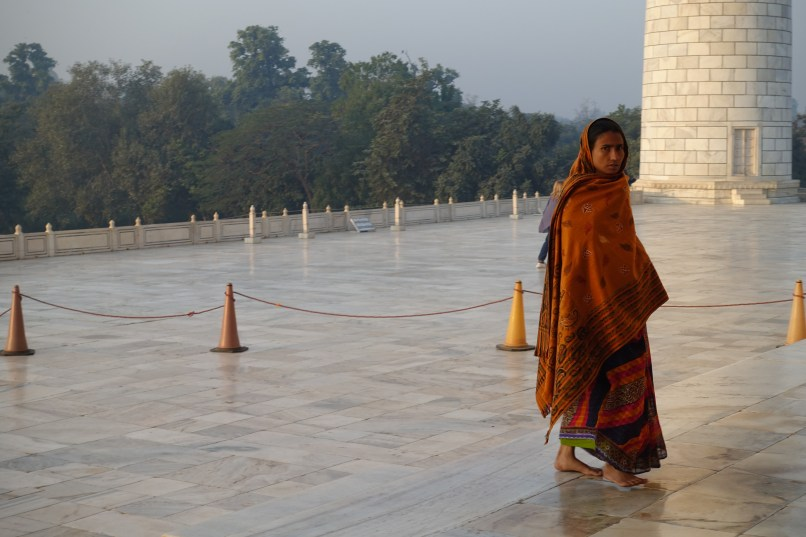 Woman in orange sari outside Taj Mahal India