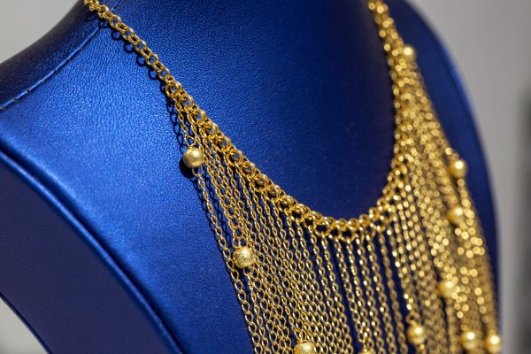 Yellow Gold Floating Balls Dangles Necklace angle view up close on a blue display element.