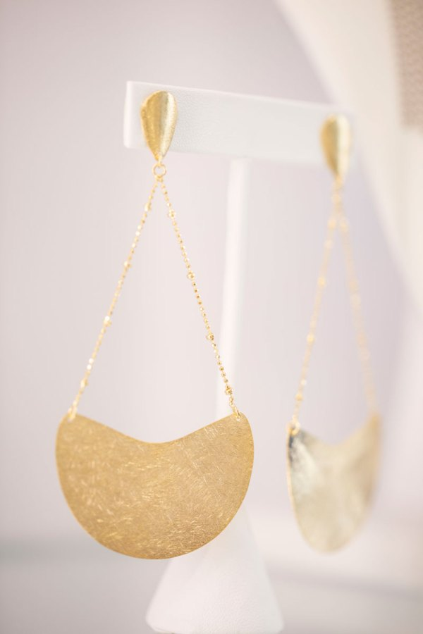 18KY Plated Half Moon Dangle Earrings on an element in showroom.