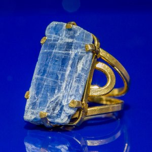 Rough Kyanite Ring on a blue reflective surface.