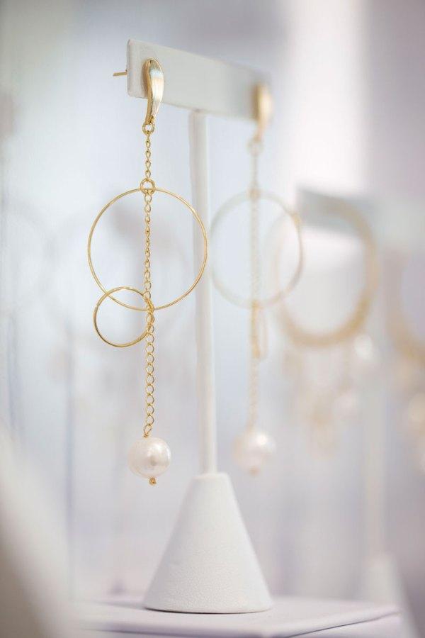Yellow Gold Hoops & Pearls Long Dangle Earrings on an element in showroom.