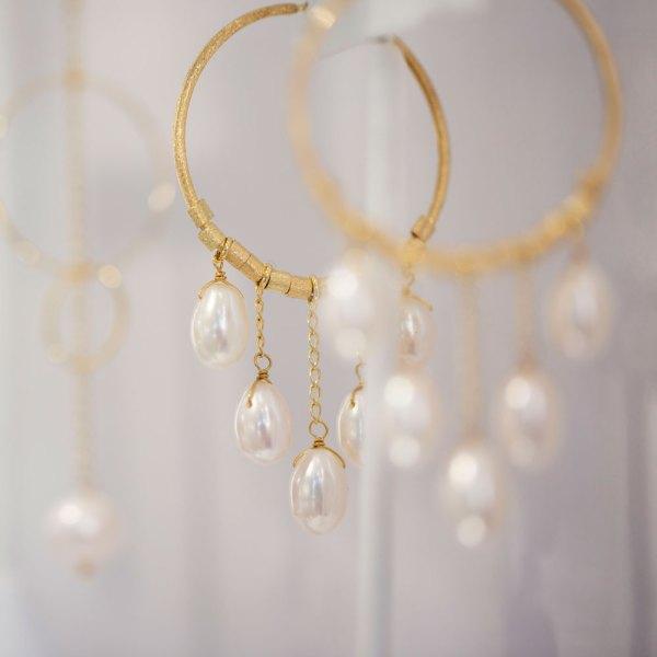 Yellow Gold Pearl Drop Hoop Earrings on an element in showroom.