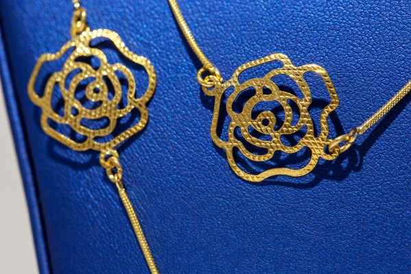 Yellow Gold Small Roses Necklace close up on roses.