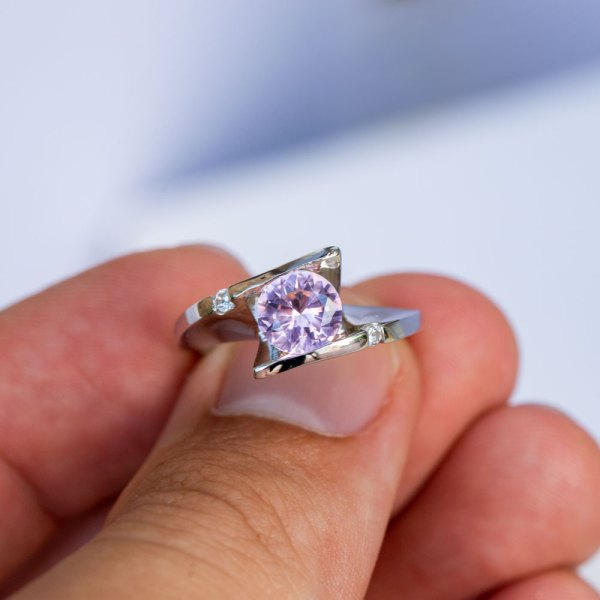 Sunset Quartz & White Sapphire Ring held between the fingers of a model.