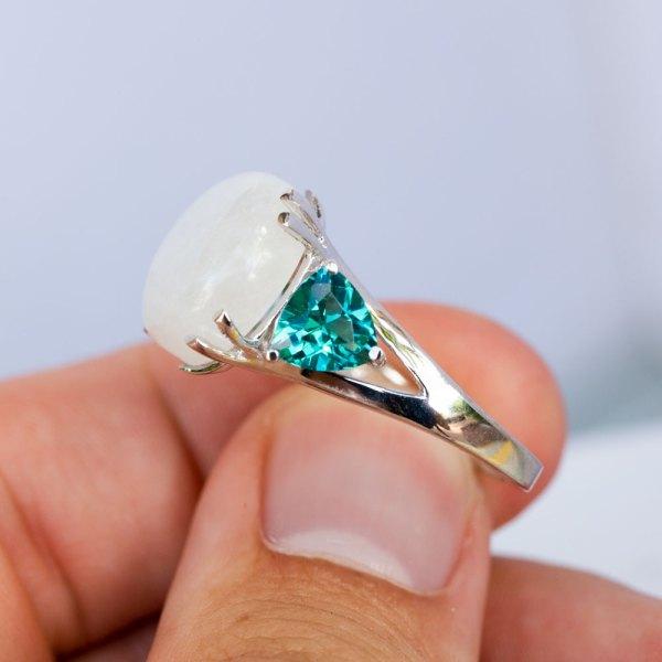 Moonstone Caribbean Blue Quartz Ring held between the fingers of a model.