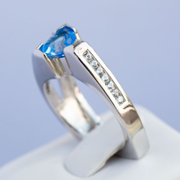 Kashmir Blue Topaz & White Sapphire Ring side view standing in a white display element.
