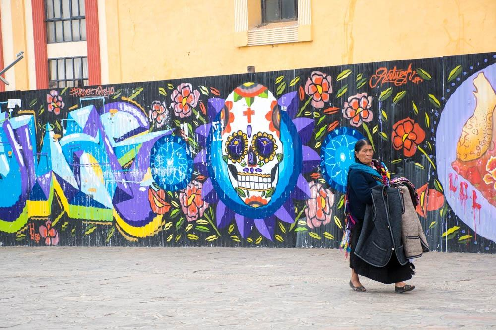 Local lady from San Cristobal de las Casas in front of the graffiti wall (One month Mexico Itinerary)
