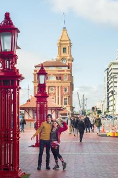 Rdeče ulične svetilke, v ozadju velika oranžno-rumena stavba s stolpom (terminal za trajekte v Aucklandu)