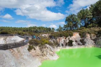 Fluoresecentno zelena mlaka, ob njej lesena brv z ograjo, na njej turisti - geotermalni park Waiotapu